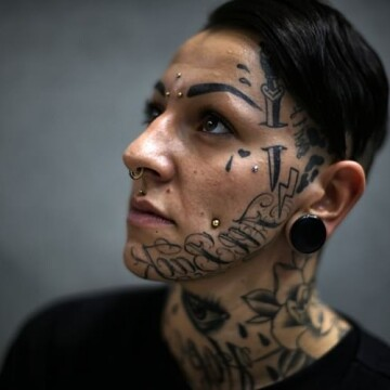 A girl poses with her tattoos during the Italian Tattoo Artists Convention at the Palavela, on September 19, 2015 in Turin.  AFP PHOTO / MARCO BERTORELLO        (Photo credit should read MARCO BERTORELLO/AFP/Getty Images)